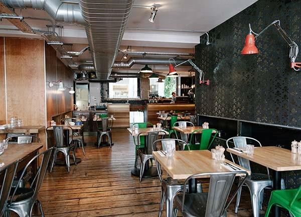 دکوراسیون صنعتی کافی شاپ با لولههای در معرض دید و میز و صندلی فلزی