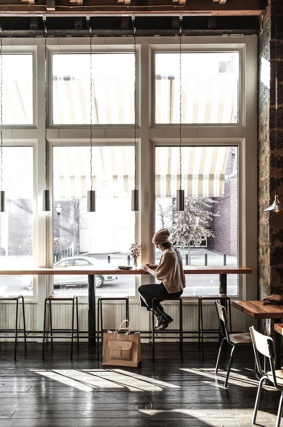 کافی شاپی با چراغهای آویزان و میز و صندلی ساده