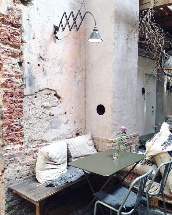 دکوراسیون صنعتی با دیوارهای آجری و صندلی فلزی و کوسن که فضا را متوزانتر کرده است